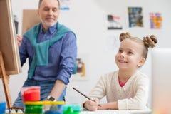 Le grand-parent et l'enfant mignons dessinent avec joie Photographie stock
