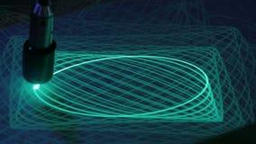 Le grand pendule dessine des ellipses avec la lumière sur la surface de phosphore
