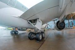 Le grand revêtement moderne d'avion d'avions s'est garé à l'aéroport, vue des roues train d'atterrissage, aile, moteur de châssis Photo libre de droits
