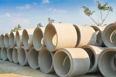 Le grandi pile di tubi di scarico concreti sulla terra preparano per il fondo sotterraneo del cielo blu e di instalation fotografia stock libera da diritti