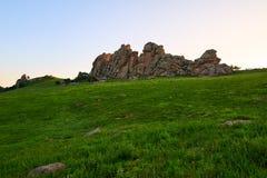 Le granit énorme sur le coucher du soleil alpin de pré Photographie stock