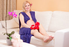 Le gravida kvinnan på en soffa Royaltyfri Foto