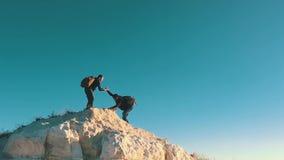 Le grimpeur aidant l'équipier à s'élever, l'homme avec le sac à dos a atteint un coup de main à son ami Ami de aide de randonneur clips vidéos