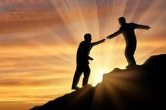 Le grimpeur aide l'ami en montagnes de donner le coucher du soleil de coup de main Photographie stock