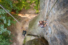 Le grimpeur de roche de femme s'élève sur un mur rocheux Photos stock