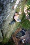 Le grimpeur de roche musculaire s'élève sur le mur de falaise avec la corde Images stock