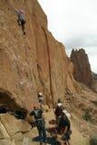 Le grimpeur de roche travaille sa manière vers le haut d'une falaise pure Photos libres de droits