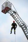 Le grimpeur des sapeurs-pompiers avec le casque rouge tombe de l'échelle TR images libres de droits
