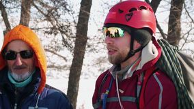 Le grimpeur expérimenté se tient avec sa bande au bord de la forêt et briefing avant d'aller et sourire banque de vidéos