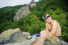 Le grimpeur masculin atteint pour un coup de main de son associé Image stock