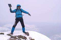 Le grimpeur placé sur une montagne jette l'ordinateur portable dans l'abîme photos libres de droits