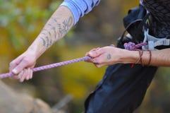 Le grimpeur tatoué saisit la corde pour descendre en rappel en bas du visage de montagne Photographie stock libre de droits