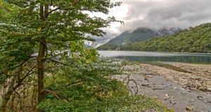 Le gris de lac mountain opacifie les collines vertes et les arbres images stock
