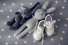 Le gris deux a tricoté des chaussures de lapin de jouet et de blanc du ` s d'enfants Photographie stock