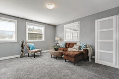 Le gris modifie la tonalité le coin salon avec le sofa brun confortable Photos libres de droits