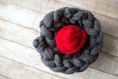 Le gris a tricoté l'écharpe de la laine mérinos avec une boule de laine mérinos rouge Photographie stock libre de droits