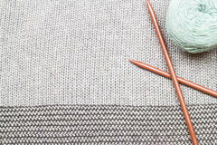 Le gris a tricoté le tissu fait de fil heathered avec les fourchettes de tricotage a Photos stock