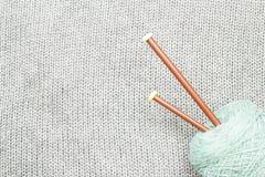 Le gris a tricoté le tissu fait de fil heathered avec les fourchettes de tricotage a Images stock