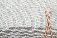 Le gris a tricoté le tissu fait de fil heathered avec les fourchettes de tricotage b Images stock