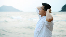 Le gros homme asiatique adulte dans la chemise blanche se sentant découragée du dur labeur trouve la détente et la méditation par Image libre de droits