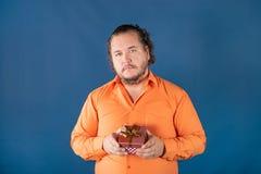 Le gros homme drôle dans la chemise orange ouvre une boîte avec un cadeau photos libres de droits