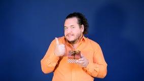 Le gros homme drôle dans la chemise orange ouvre une boîte avec un cadeau clips vidéos