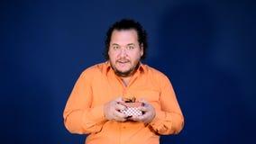 Le gros homme drôle dans la chemise orange ouvre une boîte avec un cadeau Joyeux anniversaire et grande surprise banque de vidéos