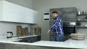 Le gros homme drôle est entré dans gaiement la cuisine avec un sourire sur son visage Danse heureuse barbue de type dans le mouve banque de vidéos