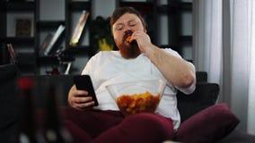 Le gros homme sourit tandis qu'il lit quelque chose dans son smartphone et mange des pommes chips banque de vidéos
