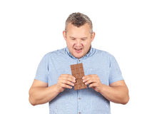 Le gros homme veut prendre une morsure de chocolat Images libres de droits