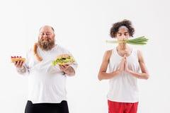 Le gros lard masculin et le type maigre préfèrent la consommation différente Photo stock