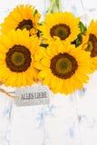 Le groupe avec les tournesols jaunes et la carte avec le texte allemand, Alles Liebe, signifie meilleurs voeux Image stock