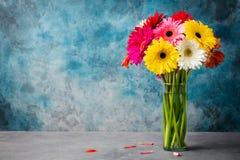 Le groupe coloré de gerbera fleurit dans un vase en verre Fond de pierre bleue Copiez l'espace Photo stock