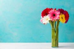 Le groupe coloré de gerbera fleurit dans un vase en verre Fond pour une carte d'invitation ou une félicitation Copiez l'espace Photographie stock libre de droits