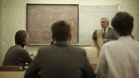 Le groupe d'étudiants dans une salle de classe, écoutant en tant que leur professeur tient une conférence clips vidéos