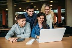Le groupe d'étudiants universitaires étudiant dans la bibliothèque d'école, une fille et un garçon utilisent un ordinateur portab Photo libre de droits