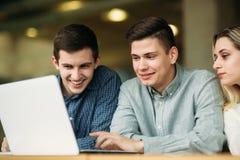 Le groupe d'étudiants universitaires étudiant dans la bibliothèque d'école, une fille et un garçon utilisent un ordinateur portab Images libres de droits