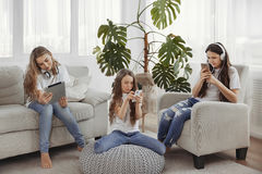 Le groupe d'adolescentes utilise des instruments Enfants avec des téléphones et des comprimés, des smartphones et des écouteurs Photo libre de droits