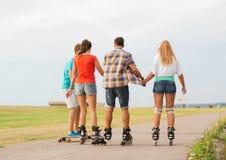 Le groupe d'adolescents avec fait du patin à roulettes Image libre de droits
