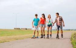 Le groupe d'adolescents de sourire avec fait du patin à roulettes Photo libre de droits