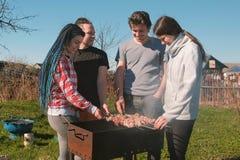 Le groupe d'amies des jeunes grillent tout entier la viande de shashlik sur le gril de charbon de bois sur l'arrière-cour Parler  Images stock