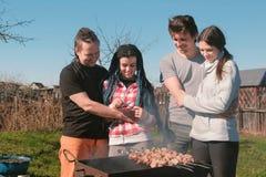 Le groupe d'amies des jeunes grillent tout entier la viande de shashlik sur le gril de charbon de bois sur l'arrière-cour Parler  Photo libre de droits