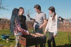 Le groupe d'amies des jeunes grillent tout entier la viande de shashlik sur le gril de charbon de bois sur l'arrière-cour Parler  Images libres de droits