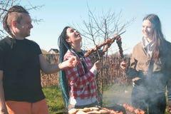 Le groupe d'amies des jeunes grillent tout entier la viande de shashlik sur le gril de charbon de bois sur l'arrière-cour Parler  Photos libres de droits