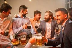 Le groupe d'amis appréciant égalisant boit avec de la bière Photographie stock libre de droits