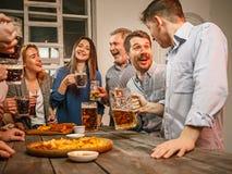 Le groupe d'amis appréciant égalisant boit avec de la bière Photo stock