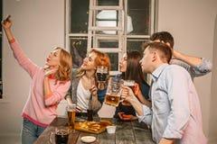 Le groupe d'amis appréciant égalisant boit avec de la bière Photo libre de droits