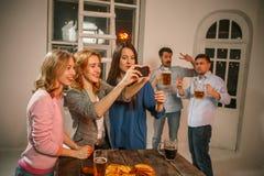Le groupe d'amis appréciant égalisant boit avec de la bière Image libre de droits