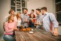 Le groupe d'amis appréciant égalisant boit avec de la bière Image stock