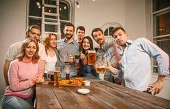 Le groupe d'amis appréciant égalisant boit avec de la bière Photos stock